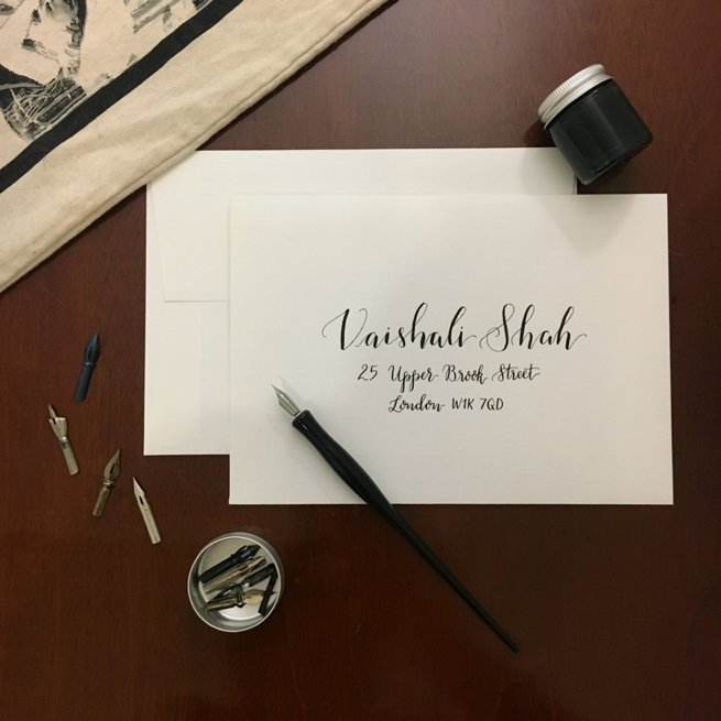 Black calligraphy writing on a white envelope with calligraphy pen | Kelly Chandler Consulting