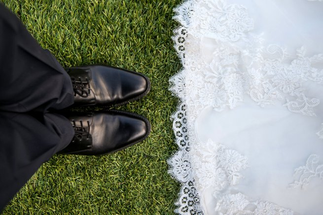 Looking down at a bride and grooms shoes   Kelly Chandler Consulting