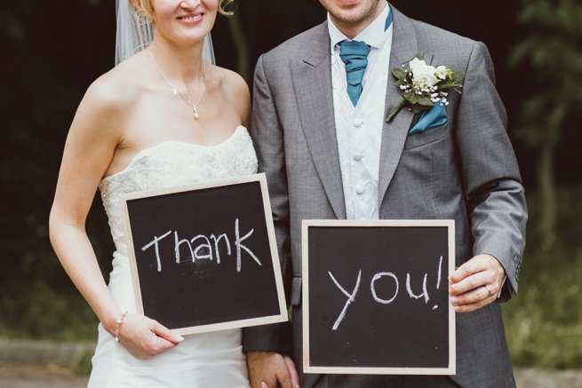 Bride and groom holding thank you chalk board signs   Kelly Chandler Consulting