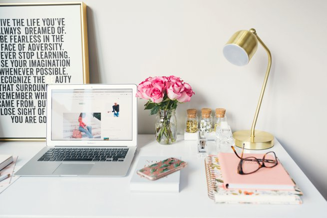 Styled desk with laptop roses in a vase and stacked books with glasses on top   Kelly Chandler Consulting