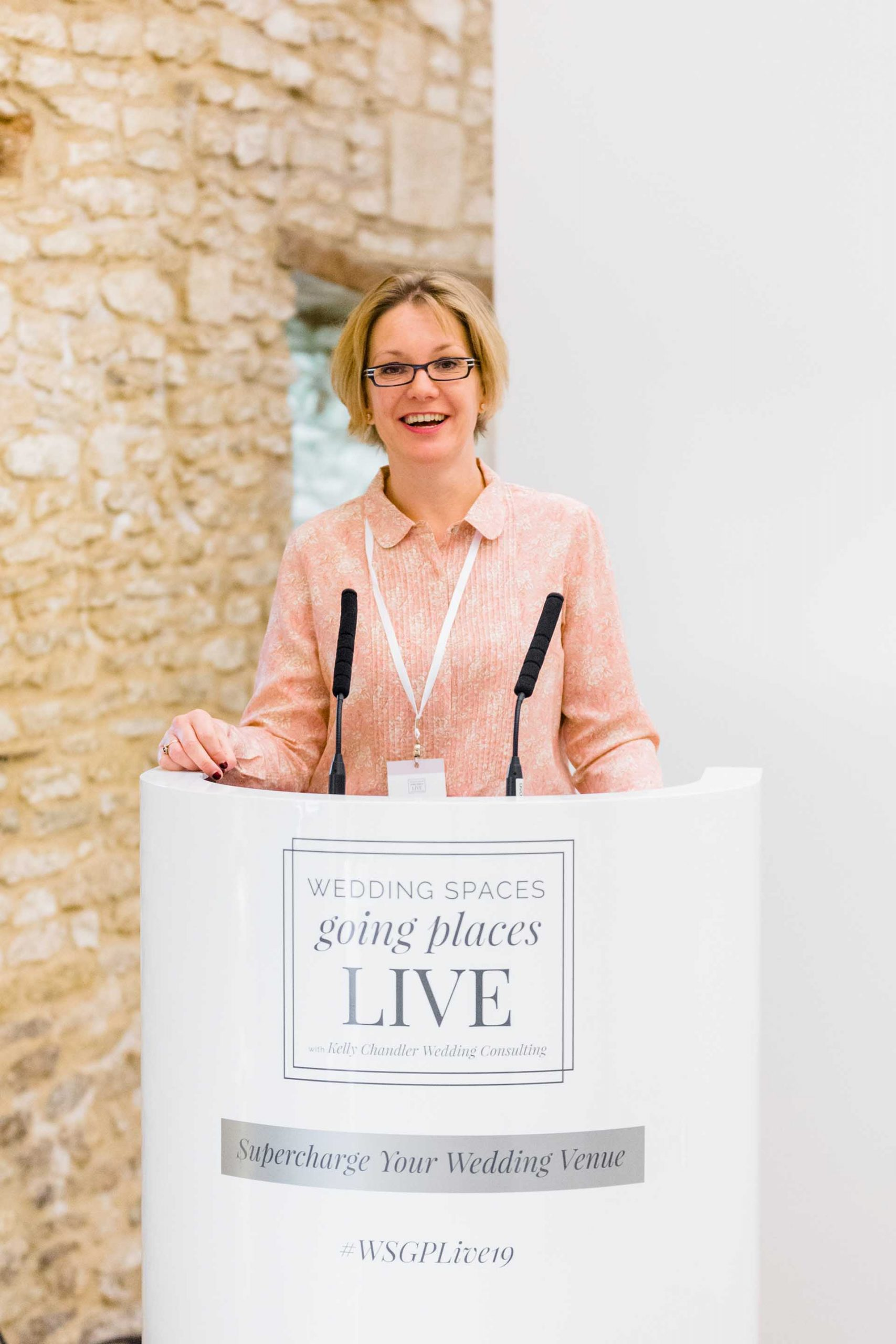 Kelly Chandler behind podium at conference for wedding venue owners
