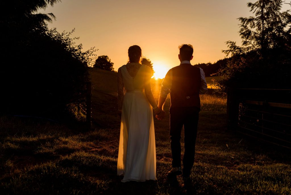 Bridal couple standing hand in hand silhouetted in sunset