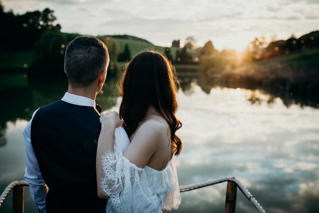 Bridal couple looking out over a sunset lake