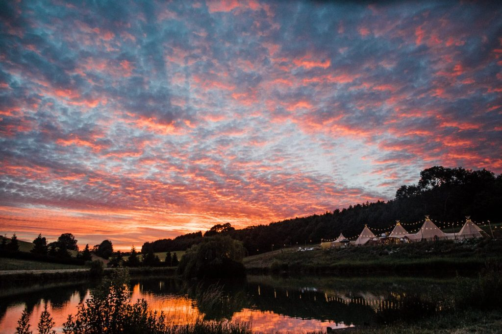 Sunset over a late with teepees on the bank