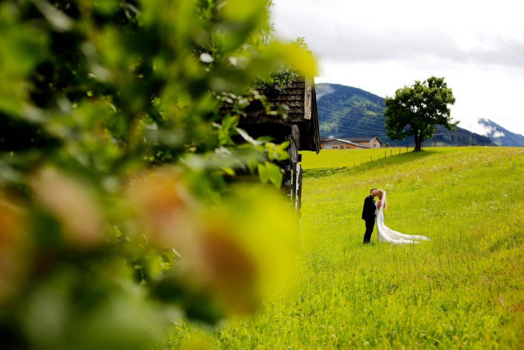 Bridal couple kissing in a green field