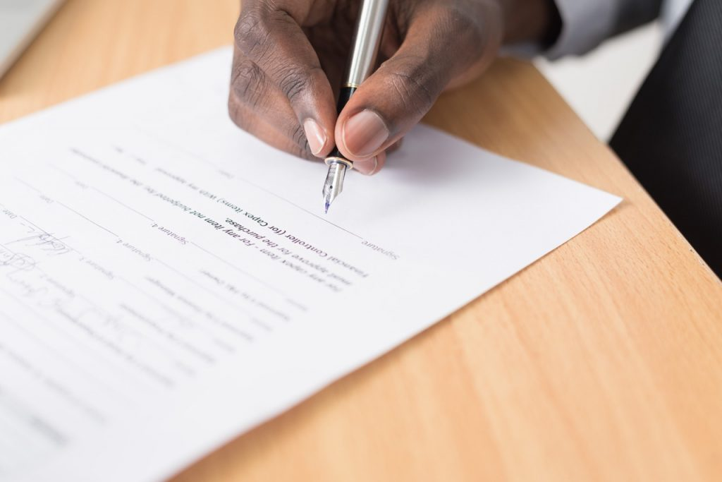 Close up of a mans hand signing a contract