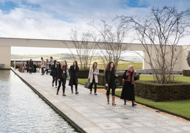 Many ladies walking along a pathway next to a modern long pond water feature