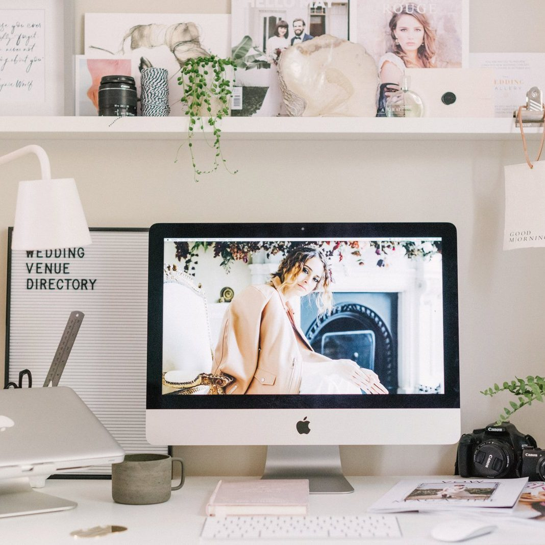 Styled work desk with apple mac plants and photo frames