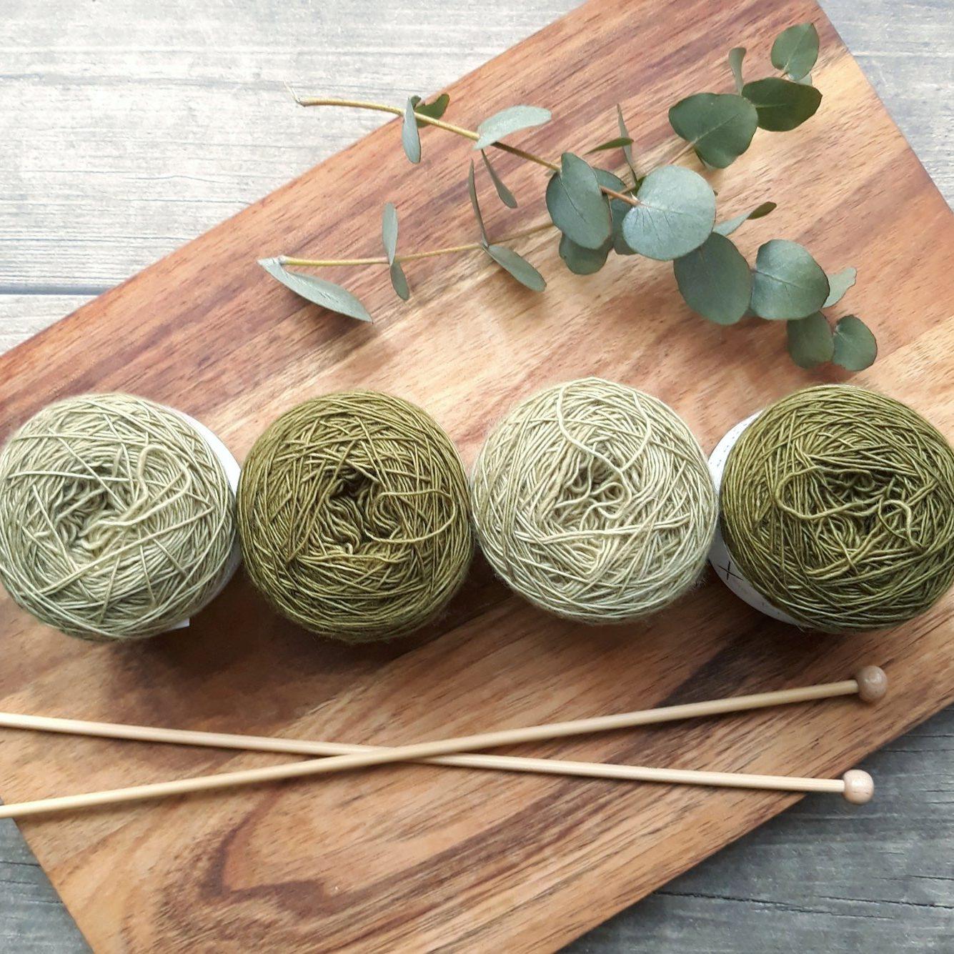 Four green balls of wool