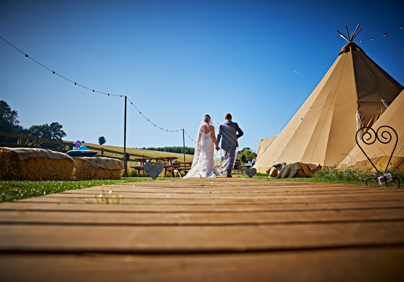 Bridal couple walking by a teepee