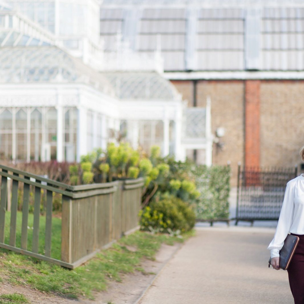 Lady standing outside a wedding venue holding a laptop