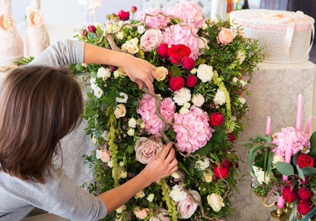 Florist at work. Woman making spring floral decorations the wedding table the bride and groom. Flowers candles a bottle of champagne. The vintage.